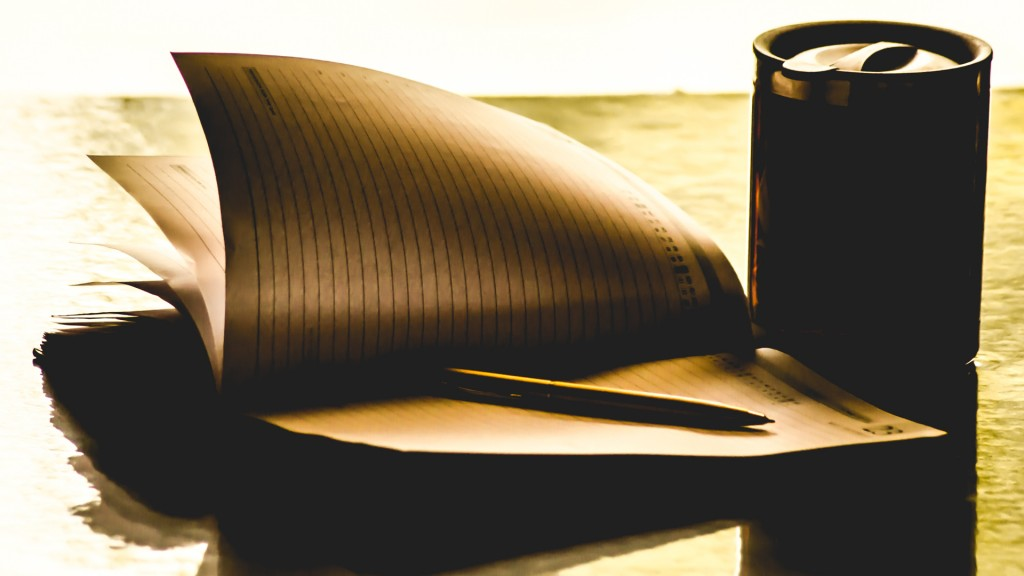 A pen kept on a diary with swirling pages with a coffee mug beside it.