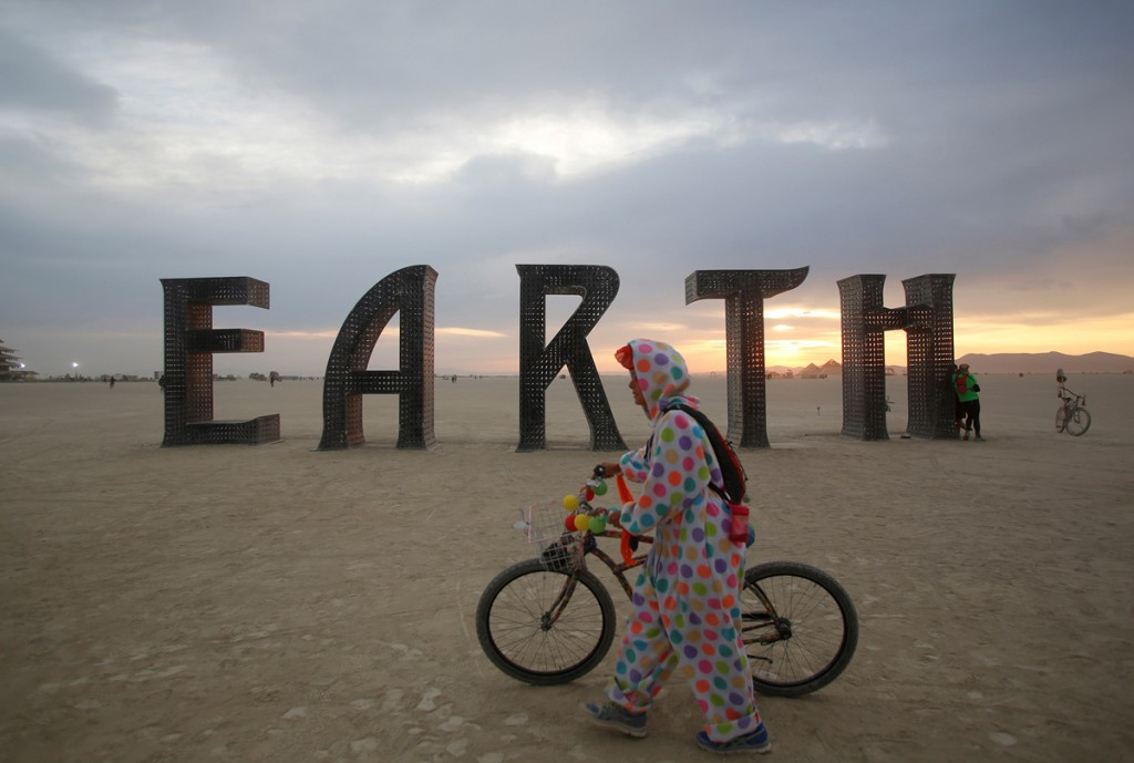 A participant walks past an art installation as approximately 70,000 people from all over the world gather for the 30th annual Burning Man arts and music festival in the Black Rock Desert of Nevada, U.S.
