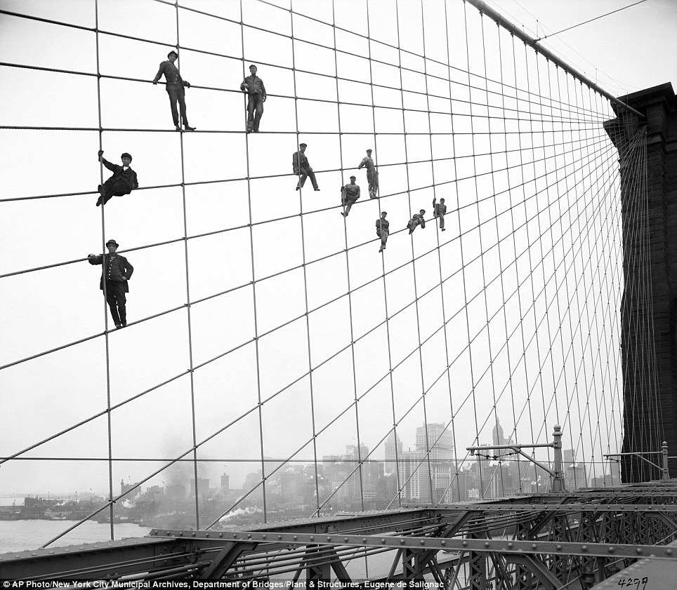Painters hang from suspended wires on the Brooklyn Bridge October 7, 1914, 31 years after it first opened.